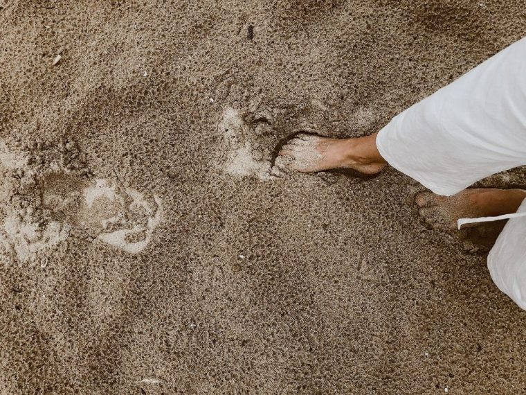 Foot in the sand with footprints