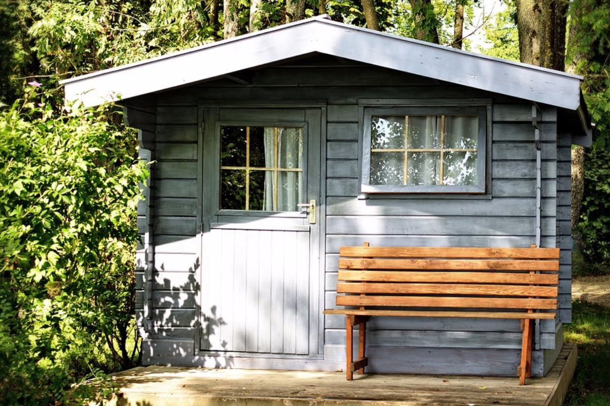 A shed with a bench outside