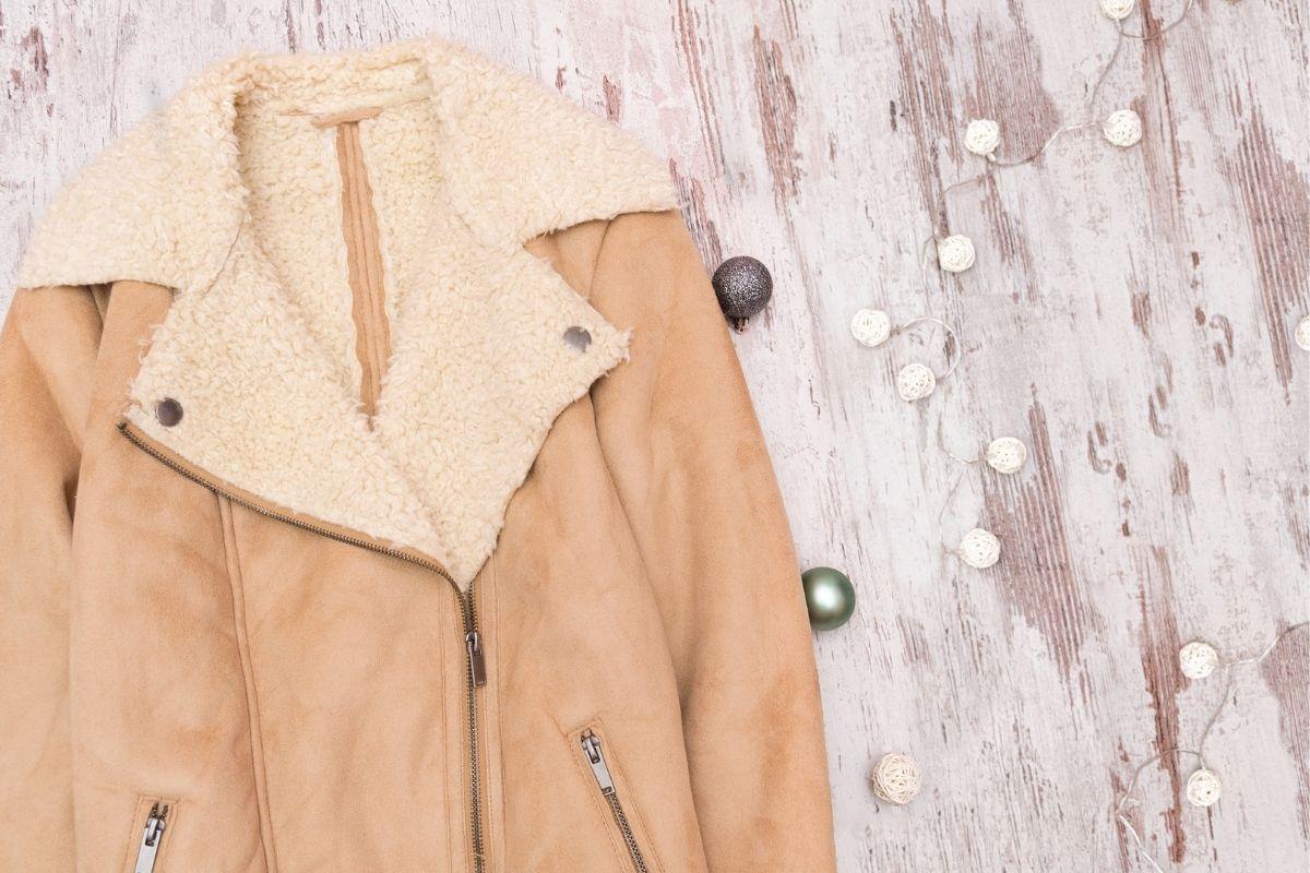 Beige winter coat in lights beside it
