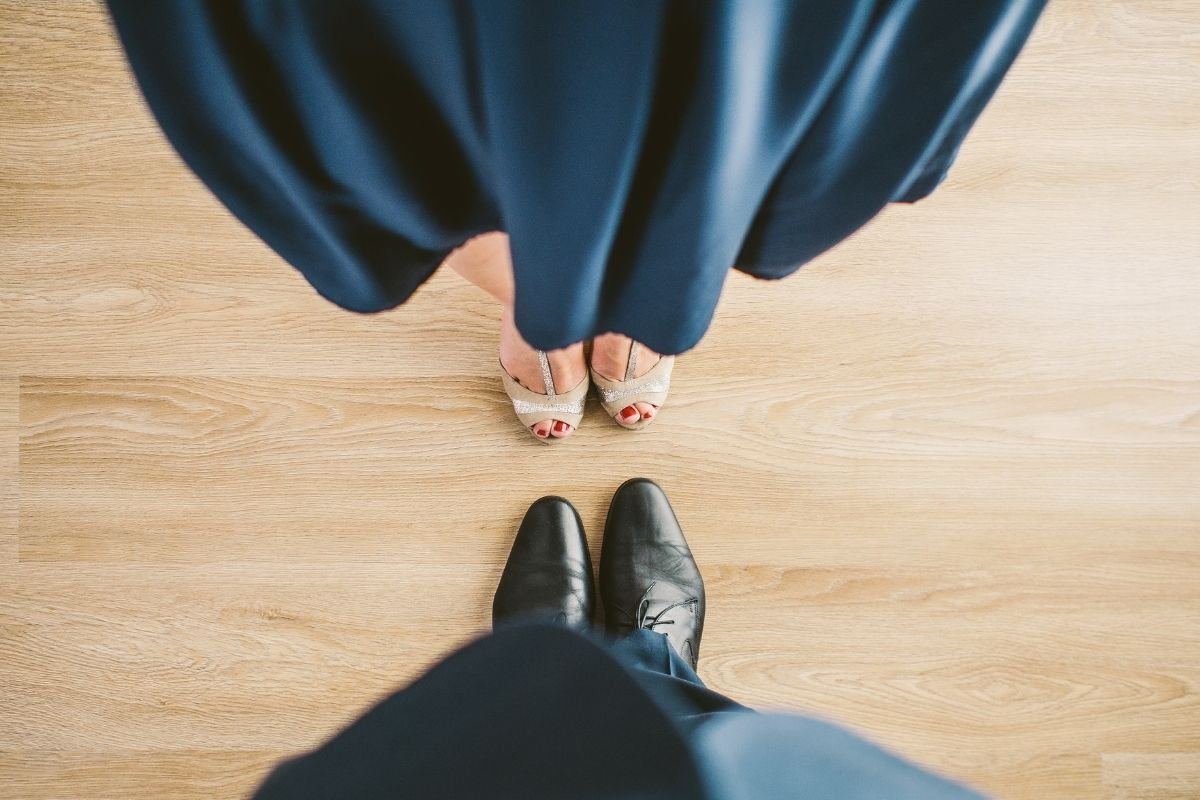 Lady in blue dress with white shoes and man in black shoes