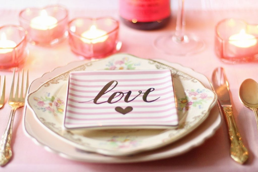"""Two white plates with """"love"""" written on lined paper"""