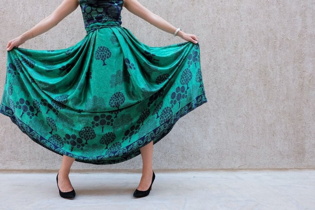 Lady in a green dress holding it out