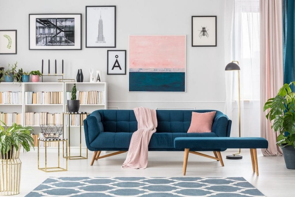 blue sofa with a white wall and pink throw